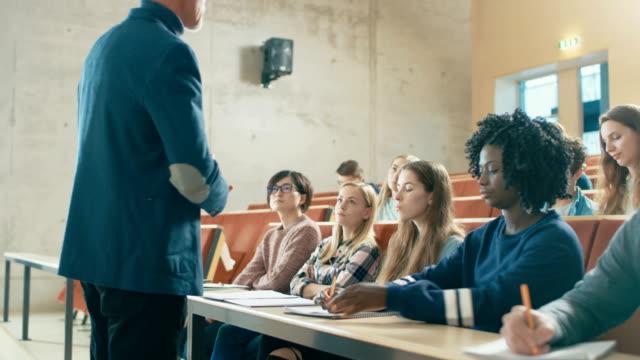 Professor-Holding-Vortrag-zu-einer-Multi-ethnischen-Gruppe-von-Studenten-Intelligente-junge-Menschen-studieren-an-der-Universität-