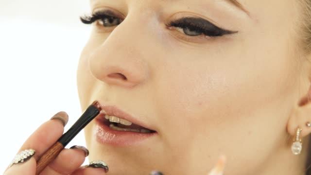 Artista-de-maquillaje-de-mano-con-labios-de-pintura-del-cepillo-cosmético-en-la-cara-de-la-mujer-Labios-maquillaje-de-cerca
