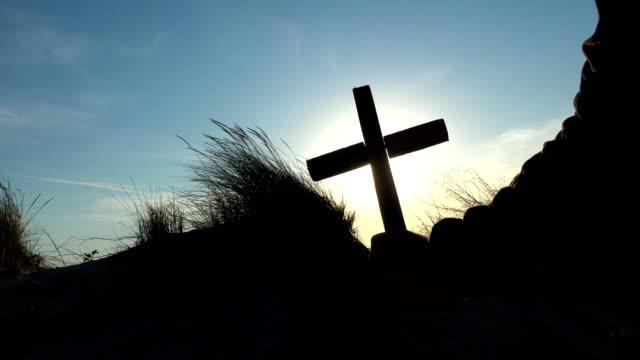 Silhouette-of-man-hand-raised-cross-over-the-sunrise---concept-for-religion
