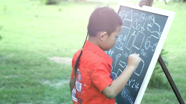 Asiatico-con-creatividad-aprender-matemáticas-dibujo-escuela-niño-Ideas-en-pizarra-negra-Fondo-de-naturaleza-verde-concepto-de-aprendizaje-Educación-de-salidas-