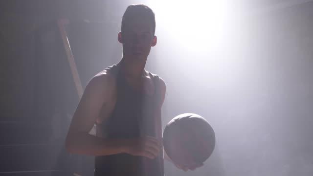 Großer-Mann-Durchführung-Basketball-Slam-Dunk-in-dunklen-Turnhalle-mit-Rauch