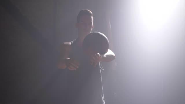 Jugador-de-baloncesto-realizando-diferentes-trucos-y-giro-bola-en-gimnasio-oscuro-con-humo