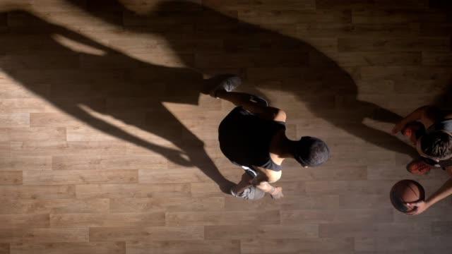 TopView-zwei-Basketball-Spieler-spielen-eins-zu-eins-im-Innenbereich