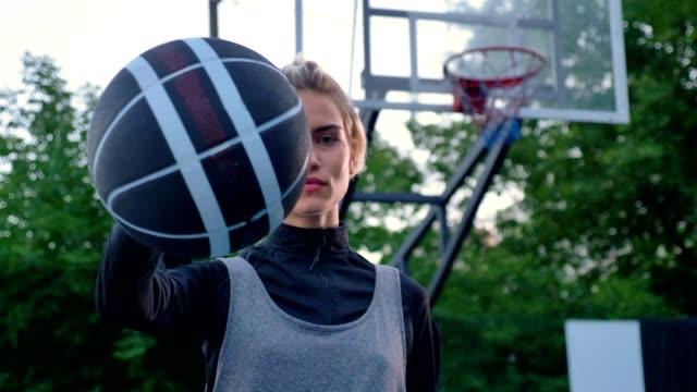 Hermosa-mujer-rubia-señalando-baloncesto-en-cámara-jugador-profesional-permanente-en-el-parque-durante-el-día-aro-en-fondo