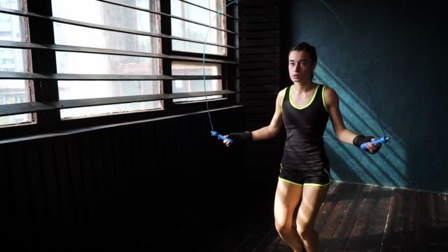 Cámara-lenta-joven-serio-boxeadora-en-manos-envueltas-calentamiento-saltando-sobre-saltar-la-cuerda-en-el-gimnasio