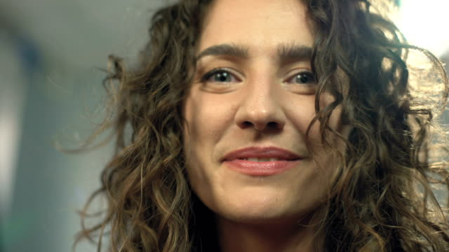 Closeup-happy-beautiful-woman-smiling-into-camera-looking-straight-to-viewer