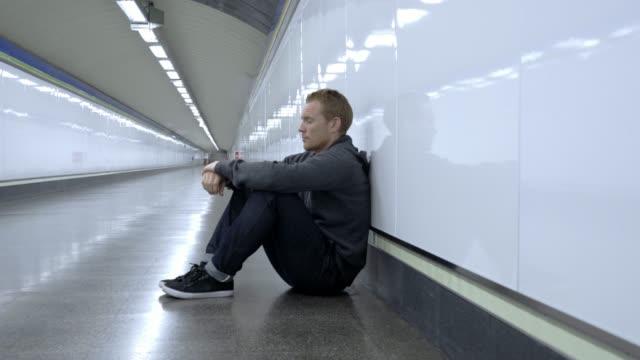 Empleo-joven-a-llorando-drogadicto-miserable-personas-sin-hogar-en-depresión-estrés-sentado-sobre-túnel-de-metro-calle-tierra-buscando-desesperada-apoyado-en-la-pared-solo-en-Trastorno-Mental-dolor-emocional-tristeza-