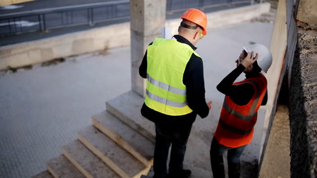 Expert-engineers-and-construction-supervisor-lift-up-the-stairs-of-construction-site-