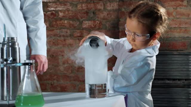 Científico-de-niño-verter-el-nitrógeno-líquido-del-termo-acero-en-vaso