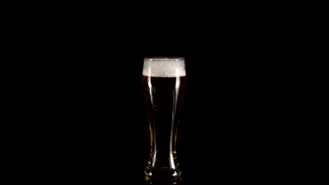 rotation-of-a-glass-of-beer-with-foam-on-a-black-background