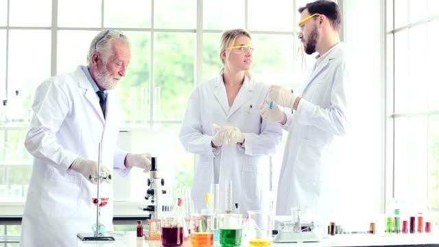 Equipo-científico-Profesor-y-los-alumnos-trabajan-con-productos-químicos-en-el-laboratorio