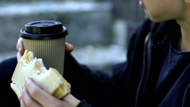 Homeless-boy-eating-sandwich-and-drinking-coffee-outdoors-poverty-closeup