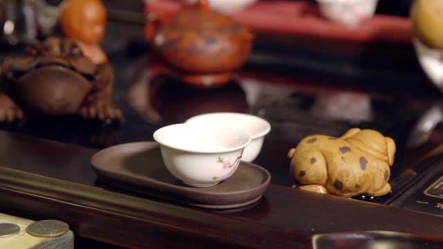 Tea-ceremony-Master-pours-tea-on-white-cups