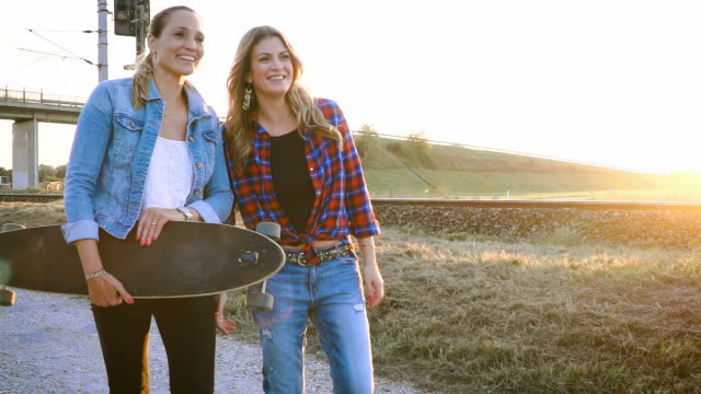 two-beautiful-and-young-women-walking-and-talking-with-skateboard