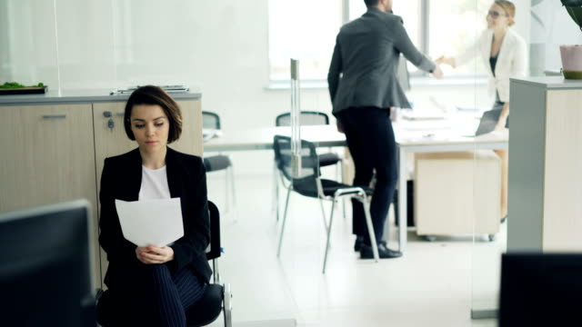 Young-attractive-woman-is-waiting-in-office-reading-her-curriculum-vitae-while-another-candidate-is-talking-to-interviewer-then-girl-is-entering-room-and-greeting-manager-