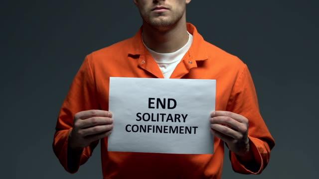 Terminar-la-frase-de-confinamiento-solitario-en-la-tarjeta-en-manos-de-prisionero-caucásico-protesta