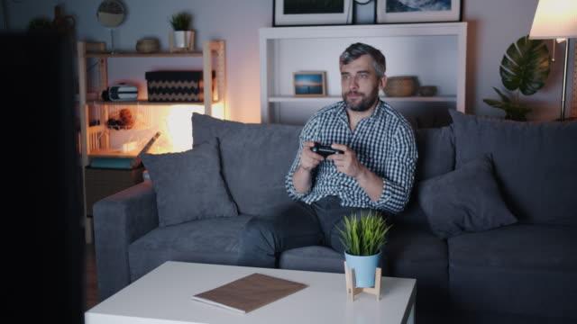 Bearded-guy-enjoying-video-game-at-home-at-night-on-sofa-holding-joystick