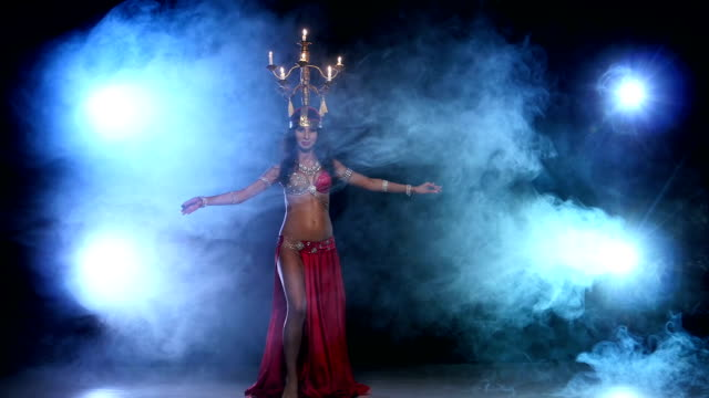 Attractive-belly-dancer-starts-dancing-with-candles-on-her-head-black-smoke
