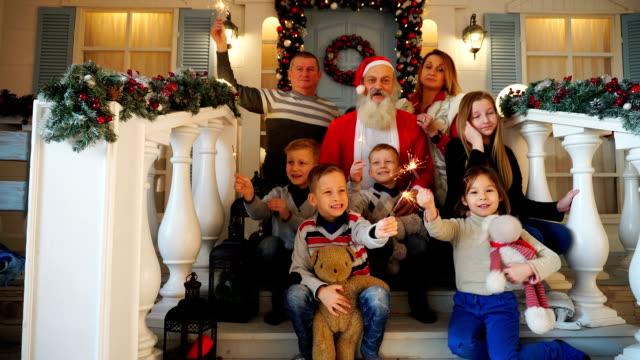 Familia-que-tiene-muchos-niños-celebrando-Noel-con-Papá-Noel