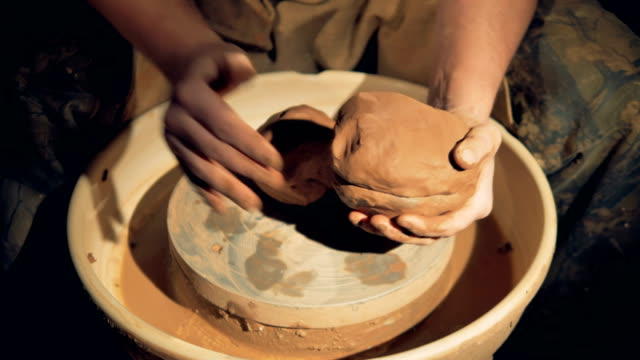 Potters-hands-shape-clay-lumps-over-a-wheel-