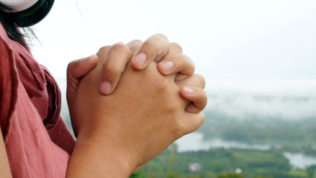 Hands-folded-in-prayer-in-a-beautiful-green-forest-with-smoke-blurred-background-