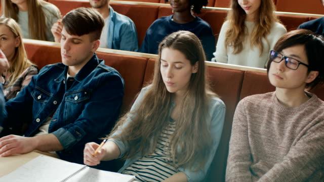Cámara-frente-a-la-clase:-Profesor-universitario-da-Conferencia-a-un-aula-llena-de-estudiantes-Multi-étnica-Profesor-Gesticulates-con-sus-manos-mientras-los-estudiantes-escuchar-