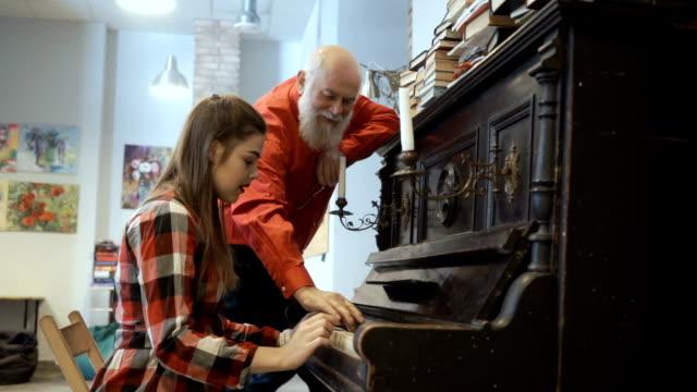 El-abuelo-escucha-nieta-juega-en-el-piano