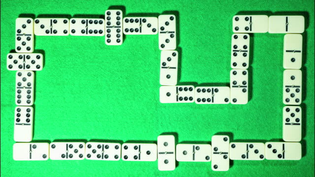 Stop-motion-of-domino-game-on-green-cloth-background-