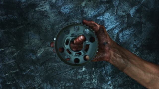 4k-Technical-Composition-of-Dirty-Mechanic-Hands-Holding-Gear