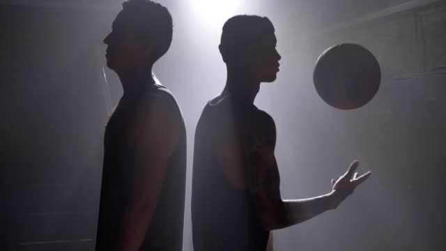 Two-basketball-players-shadow-standing-back-to-back-in-misty-room-with-floodlight