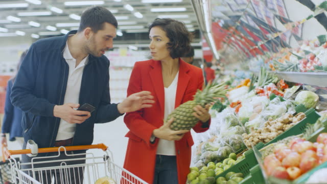 At-the-Supermarket:-Happy-Couple-Does-Shopping-Choosing-Fruits-and-Vegetables-in-the-Fresh-Produce-Section-Man-Uses-Smartphone-and-Pushes-Shopping-Cart-Woman-Places-Products-into-Trolley-