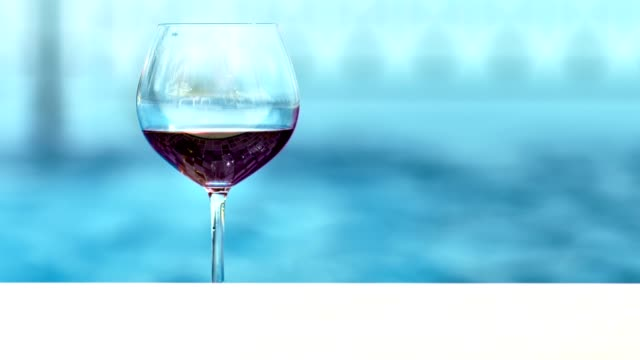 Close-up-of-red-wine-in-beautiful-glass-goblet-outdoor-in-warm-summer-sunny-day-glare-of-sea