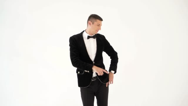 humorist-in-trendy-costume-is-parodying-a-man-who-dancing-in-a-club-on-a-white-background-in-the-studio