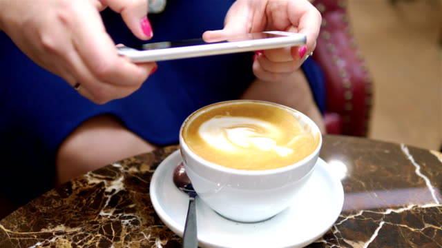 Woman-taking-a-picture-of-cup-of-latte-art-coffee-on-the-table-in-4k-slow-motion-60fps