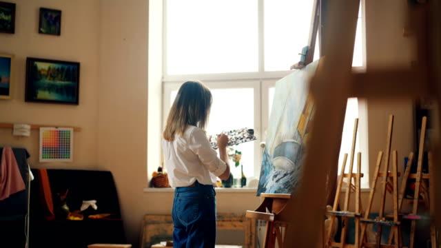 Professionelle-Maler-junge-Dame-ist-Gemälde-Seelandschaft-mit-Acrylfarben-Darstellung-Meereslandschaft-Schiff-und-Meer-Wellen-arbeiten-allein-im-Studio-Menschen-und-Arbeit-Konzept-