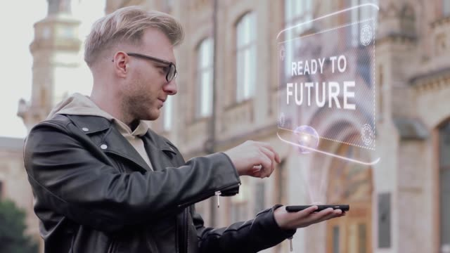 Smart-young-man-with-glasses-shows-a-conceptual-hologram-Ready-to-future