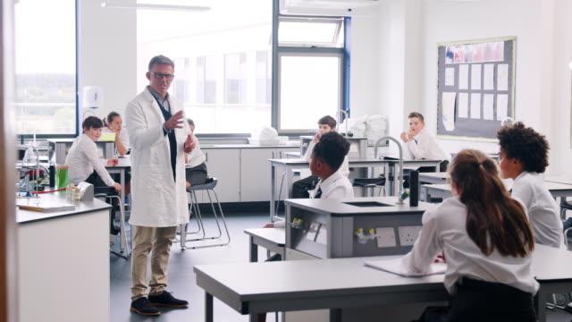 Männliche-Lehrer-Lehre-Gymnasiasten-In-Uniformen-an-Werkbänken-im-naturwissenschaftlichen-Unterricht-sitzen