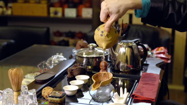 Master-pours-tea-leaves-with-water-Tea-ceremony