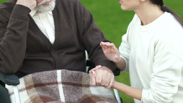 Voluntariado-de-apoyo-a-anciano-en-silla-de-ruedas-compasión-por-los-enfermos-concepto-de-caridad