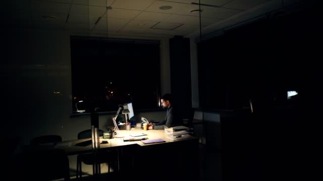 Müde-Geschäftsmann-in-Anzug-und-Krawatte-nutzt-Computer-im-Büro-arbeiten-nachts-sitzt-am-Arbeitstisch-in-dunklen-Raum-mit-Blick-auf-den-Bildschirm-und-tippen-dann-Kaffee-trinken-