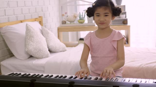 4K:-Asian-kid-girl-is-training-to-play-an-electric-piano-Is-an-activity-that-trains-emotional-skills-And-the-body-well-Study-at-home-or-music-school-Music-good-mental-health-and-good-mood-