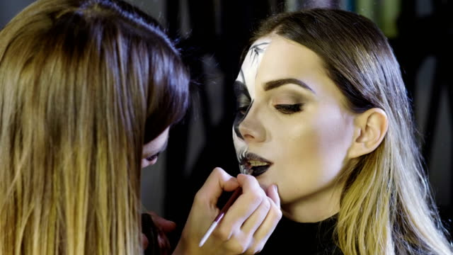 Make-up-artist-is-making-blonde-woman-up-as-dead-bride-for-Halloween-party-4K
