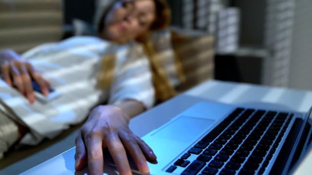 Empresaria-cansada-dormir-en-el-sofá-en-la-oficina-con-ordenador-portátil-y-teléfono