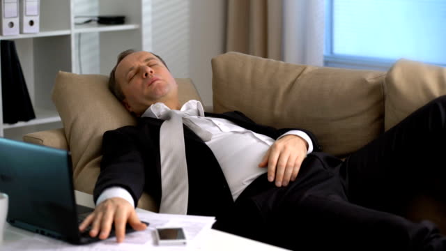 Tired-businessman-is-sleeping-on-the-sofa-at-the-office