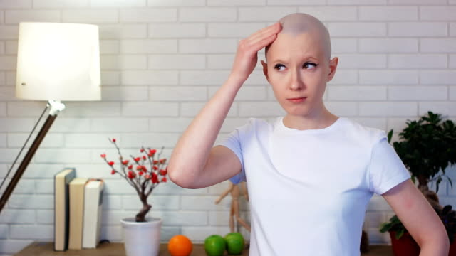 Concerned-woman-in-chemotherapy-looking-in-the-mirror-and-examine-herself