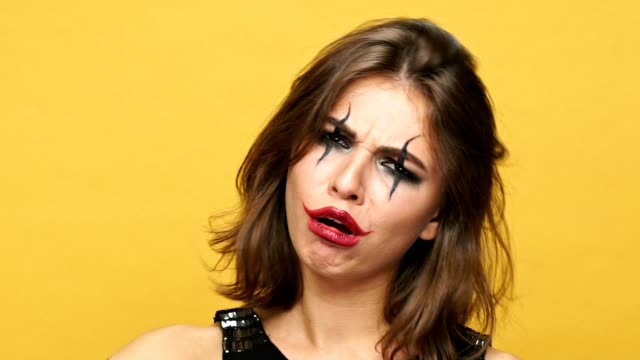 Creepy-funny-lady-with-dark-halloween-make-up-changing-different-emotions-with-hand-isolated-over-yellow
