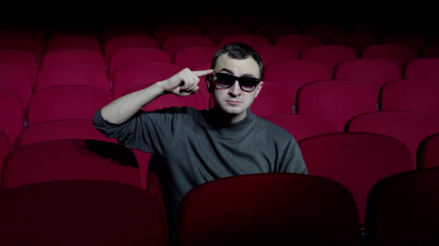 Single-man-sitting-in-comfortable-red-chairs-in-dark-cinema-theater-and-twists-her-finger-at-her-temple