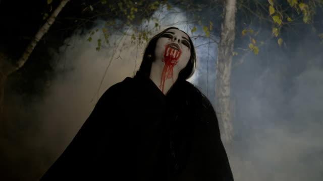 Vampiro-maléfico-zombie-mujer-saliendo-de-un-bosque-de-niebla-en-la-noche-de-la-luna-para-celebrar-halloween