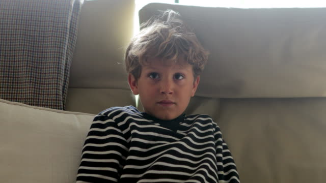 Child-face-watching-television-in-4K-Young-boy-seated-in-sofa-starring-something-behind-viewer