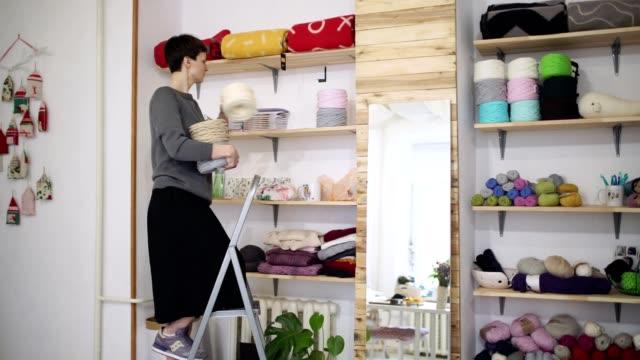 Creative-woman-shelving-thread-spool-on-stillage-in-textile-workshop